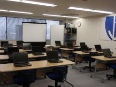 写真:Willさんいんセミナールーム。窓側にプロジェクタとスクリーン、ホワイトボード。2人掛けの長机8脚にノートパソコンが2台ずつ置いてある。